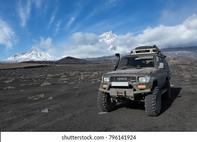 KAMCHATKA PENINSULA, RUSSIA - OCT 1, 2016: Japanese 4wd car Toyota Land Cruiser Prado prepared for long travel and off-road tourism through mountains parked on volcanic slag on background volcanoes.