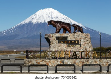 KAMCHATKA PENINSULA, RUSSIA - SEP 24, 2017: Sculpture of Kamchatka brown bear family She bear and bear cub, inscription: Here begins Russia. Kamchatka. Monument to animals on background of volcano.