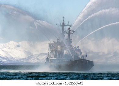 KAMCHATKA, RUSSIA - APR 27, 2019: Rescue and salvage ship of Pacific Fleet of Russia spraying water on sea for supporting emergency case of fire of warships, passengers, cargo ships, oil tanker.