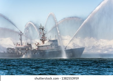 KAMCHATKA, RUSSIA - APR 27, 2019: Rescue and salvage ship of Pacific Fleet of Russia spraying water on sea for supporting emergency case of fire of warships, cargo ships, oil and gas industry.