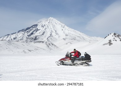 Kamchatka, Russia - Mar 17, 2015 : Unidentified asian tourist  driving snow mobile with the snowy mountain landscape.