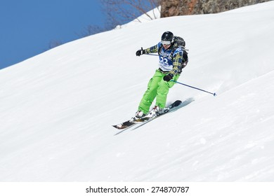 """KAMCHATKA, RUSSIA - MARCH 9, 2014: Girl skier rides steep mountains. Competitions freeride skiers and snowboarders """"Kamchatka Freeride Open Cup"""". Russia, Far East, Kamchatka Peninsula."""