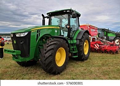 KAMEN, CZECH REPUBLIC - September 10, 2013: John Deere tractor with attached Pottinger seeder, cloudy sky on background