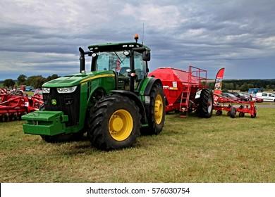 KAMEN, CZECH REPUBLIC - September 10, 2013: John Deere tractor with attached corn seed drill Pottinger, cloudy sky