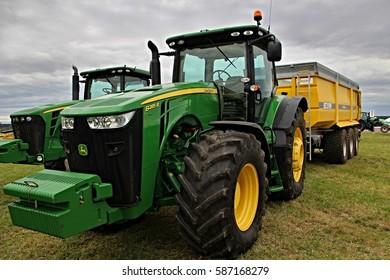 KAMEN, CZECH REPUBLIC - September 10, 2013: John Deere tractor with yellow trailer, cloudy sky on background