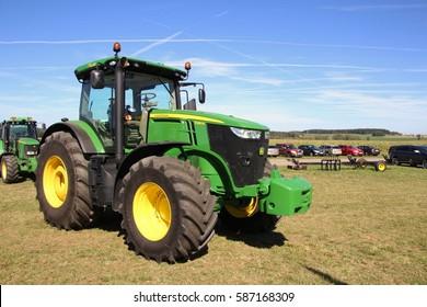 KAMEN, CZECH REPUBLIC - September 10, 2013: John Deere tractor on grass field, blue sky on background