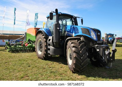 KAMEN, CZECH REPUBLIC - September 10, 2013: New Holland tractor with Amazone sowing machine, grass field, blue sky and flags on background