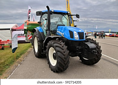 KAMEN, CZECH REPUBLIC - September 10, 2013: Small New Holland tractor on asphalt with attached Amazone fertilizer, spacious cabin, cloudy sky on background