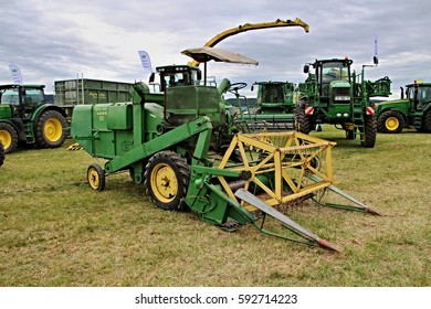 KAMEN, CZECH REPUBLIC - September 10, 2013: Old John Deere combine from 20th century, small header, ancient agricultural machinery, rust on metal, new tractors in the background, green colour