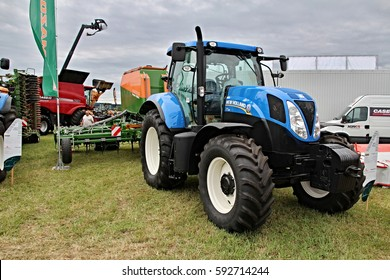 KAMEN, CZECH REPUBLIC - September 10, 2013: New Holland tractor with attached Amazone seeder for corn and sugar beet, old design, big tyres with new tread, cloudy sky in the background