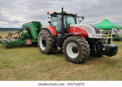 KAMEN, CZECH REPUBLIC - September 10, 2013: Big Steyr tractor with attached Great Plains seeder for corn, barley and wheat, white bonnet, big tyres with new tread, before storm