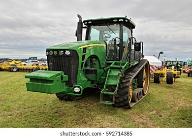 KAMEN, CZECH REPUBLIC - September 10, 2013: John Deere tractor with belts, better traction, attached tilling tool for compacting the soil, dramatic sky in the background