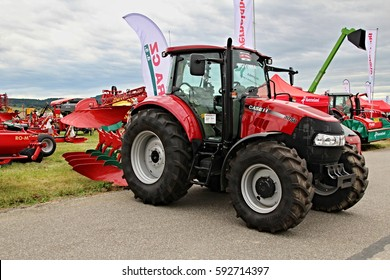 KAMEN, CZECH REPUBLIC - September 10, 2013: Small Case IH tractor with attached red plough, spacious cabin, cloudy sky in the background