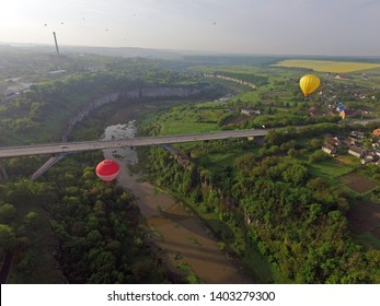Kamianets-Podilsky, Ukraine - May 18, 2019: Colorful hot air balloons fly near bridge during aeronautic spring festival. Vacation in sky, aeronautic adventures. River meandr, aerial view.