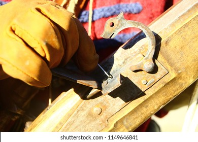 Kamianets-Podilsky, Ukraine - October 1, 2016: Hand of musketeer in yellow leather glove. Preparing hand-made rifled musket before battle reenactment on living history festival. Flintlock mechanism.