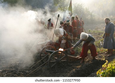 KAMIANETS-PODILSKY, Ukraine - October 3, 2009. Brigade of cannoneers in uniforms of Russian archers shoot cannons in smoke at reenactment of battle at living history festival.
