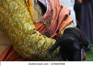 Kamianets-Podilsky, Ukraine - September 29, 2018: Details of rich brocade costume of the nobleman in 17th century. Leather gloves, golden chain. Prince or warlord. Living history festival.