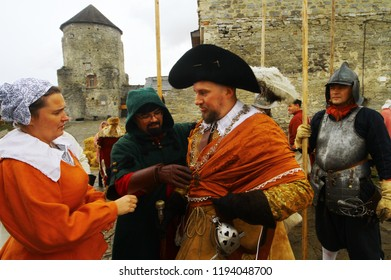 Kamianets-Podilsky, Ukraine - September 29, 2018: Wife and a monk helping to dress up a rich nobleman in brocade costume and broad-brim. Warlord goes to battle. Living history festival.