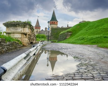 Kamianets-Podilskyi fortress built in the 15th century. Road covered with cobbles to the castle and remains of old city gates after rain, Khmelnytskyi oblast, Ukraine