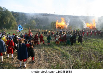 Kamianets-Podilsky,Ukraine - October 4, 2008: wooden houses are on fire during  historical reenactment. Living history festival. Troops and peasants stand in cannon smoke before the final big battle.