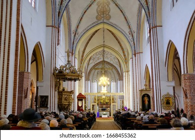 Kamien Pomorski, Poland - circa November 2019: Interior of the Co-Cathedral of St. John the Baptist and people sitting on the pews during mass.