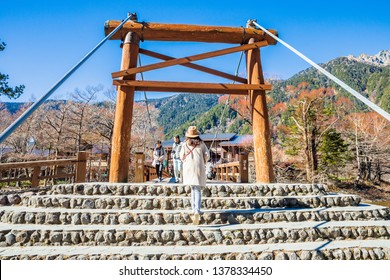 KAMIKOCHI,NAGANO,JAPAN-NOVEMBER 15,2018: Female tourist walking on the kappa wooden bridge at Kamikochi, the northern part of the Japan Alps. Beautiful scenery .