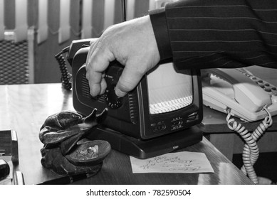 Kamin, Volyn / Ukraine - October 06 2008: Hand of man with a small TV in the office