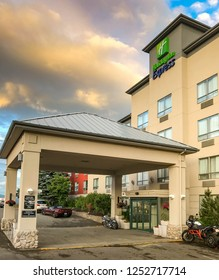 KAMLOOPS, BRITISH COLUMBIA, CANADA - JUNE 2018: Wide angle view of the entrance of the Holiday Inn Express hotel in Kamloops, with colored clouds in the sky at dusk.