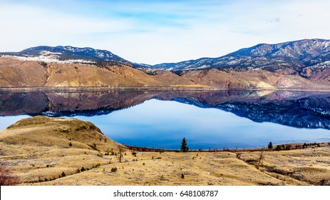 Kamloops Lake, which is a very wide portion of the Thompson River, on a cold winter day with the surrounding mountain reflecting in the quiet surface of the lake.