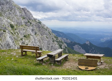 Kamnik saddle ( Kamnisko sedlo ), Kamnik-Savinja Alps, Slovenian Alps, Slovenia, Europe -  rustic wooden bench, table and beautiful nature with rocky peaks