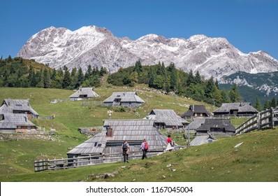 KAMNIK, SLOVENIA - AUGUST 27, 2018: Three woman hikers admiring cottages of Velika planina (Big Pasture Plateau)