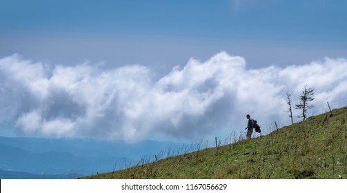 KAMNIK, SLOVENIA - AUGUST 27, 2018:  Lonely hiker in front of big white cloud on Velika planina (Big Pasture Plateau)