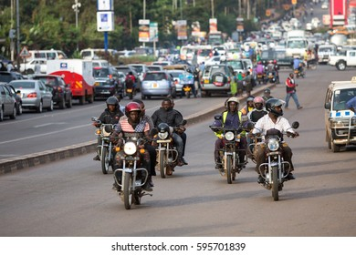 KAMPALA, UGANDA - 2016: Ugandans traveling from one destination to another by boda (motorbike taxis) on a wide avenue in the capital city. Boda is a rapid but risky mode of transport in Uganda.