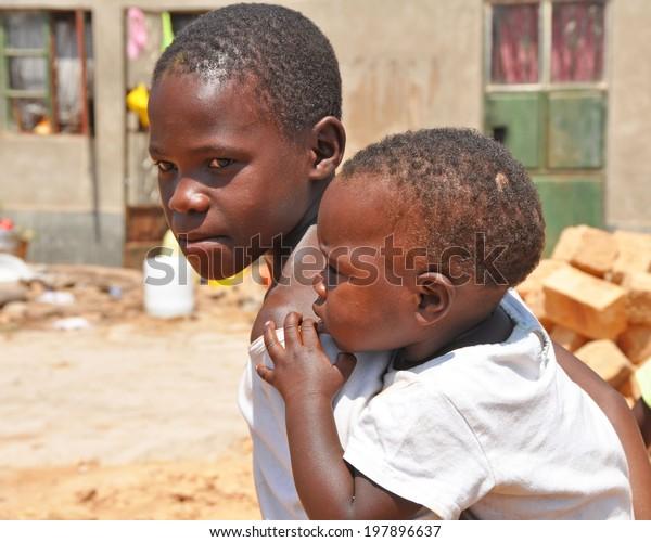 KAMPALA, UGANDA, AFRICA - CIRCA FEBRUARY 2009: Unidentified boys living in the Kampala slums circa February 2009 in Uganda, Africa. Kampala is the largest city and capital of Uganda.