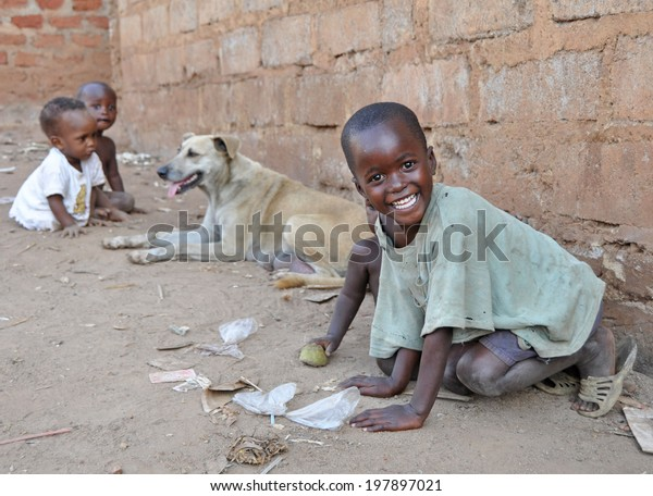 KAMPALA, UGANDA, AFRICA - CIRCA FEBRUARY 2009: Unidentified children and a dog living in the Kampala slums circa February 2009 in Uganda, Africa. Kampala is the largest city and capital of Uganda.