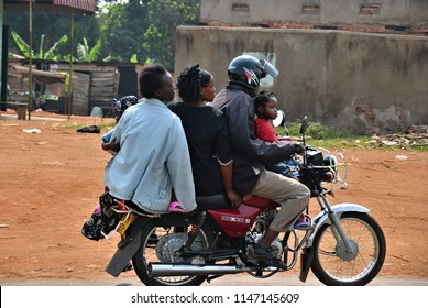 Kampala, Uganda - Aug 26, 2010: A family of five member rides a motorbike in the Kampala slums. husband, his wife, grandmother and two children. Uganda one from most poorest country in central Africa