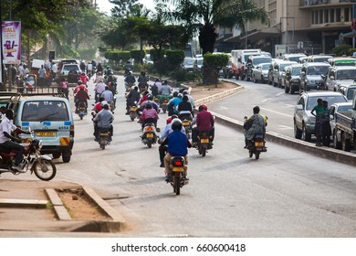 KAMPALA, UGANDA - CIRCA NOV, 2016: Ugandans traveling from one destination to another by boda (motorbike taxis) on a wide avenue in the capital city.