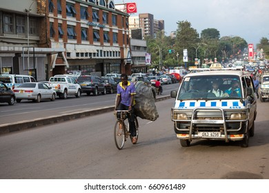 KAMPALA, UGANDA - CIRCA NOV, 2016: A man is cycling next to a minibus on road. Daily life in Kampala, Uganda.