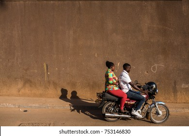 KAMPALA, UGANDA - CIRCA NOV, 2016: Ugandan woman traveling from one destination to another by boda (motorbike taxis) in the capital city.