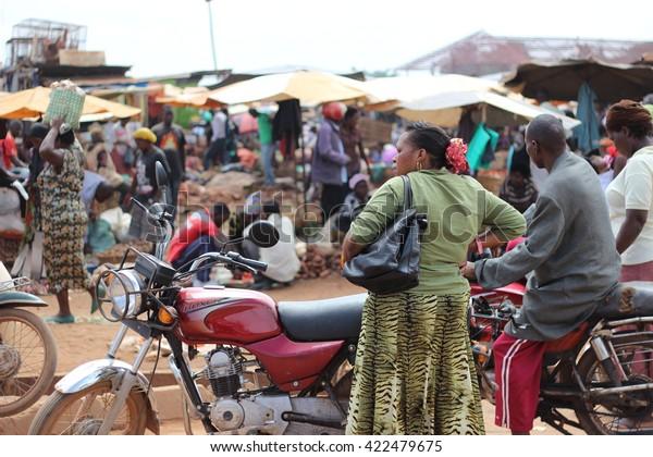 KAMPALA, UGANDA - CIRCA NOVEMBER 2015: A woman is standing by a boda boda moto driver next to a busy local market in Kampala.