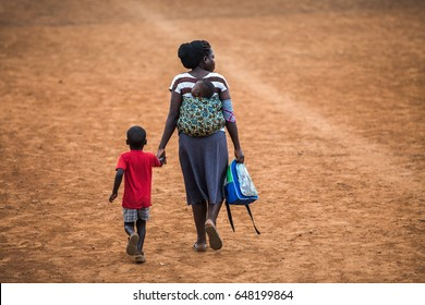 KAMPALA, UGANDA - CIRCA NOVEMBER 2016: An Ugandan mother with her baby on back, has taken her son from school and is going home.