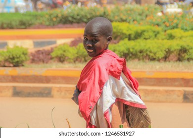 Kampala, Uganda - January 22, 2018: A local boy walks down Kampala street, turns around and smiles