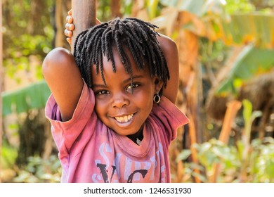 Kampala, Uganda - January 26, 2018: Ugandan African girl with dreadlocks smiles very cute while playing on the street of Kampala suburb