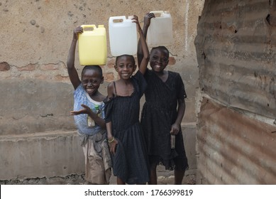 KAMPALA, UGANDA - JANUARY 26 2020: Unidentified girls with water cans pose for photo in Katanga slum, Kampala, Uganda. Doing housework instead of studying at school is a daily routine for them.