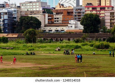 KAMPALA, UGANDA – NOVEMBER 11, 2017: People playing soccer on a field in front of offices in the city of Kampala. This is the biggest city in Uganda.