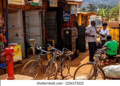 KAMPALA, UGANDA – OCTOBER 05, 2016: A few people standing in front of a shop which is inside a container. A few bikes in the foreground. This is a typical street picture of the city of Kampala.