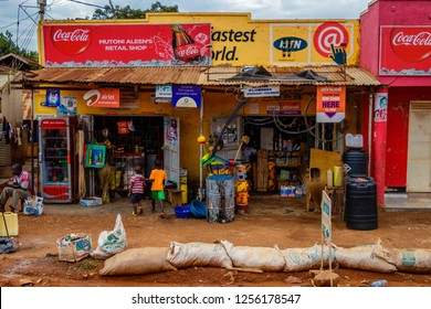 KAMPALA, UGANDA – OCTOBER 05, 2016: Few kids standing in front of a shop. Sand bags on the street to protect the shop against the mud. This is a typical street picture of the city of Kampala.
