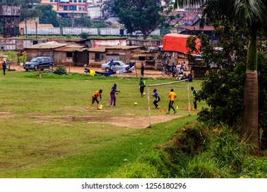 KAMPALA, UGANDA – OCTOBER 05, 2017: People playing soccer on a field in front of offices and townships in the city of Kampala. This is the biggest city in Uganda.