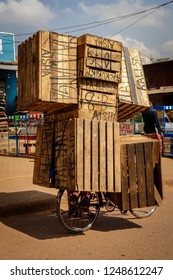 KAMPALA, UGANDA – OCTOBER 29, 2016: A man turned his bike into a carrier for crates. Transporting many crates on the road from Kampala to Entebbe