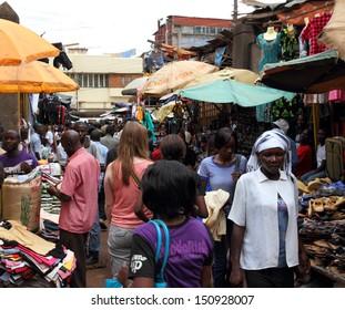 KAMPALA, UGANDA - SEPTEMBER 28, 2012.  A white woman walks away through a market shopping among locals in Kampala, Uganda on September 28,2012.
